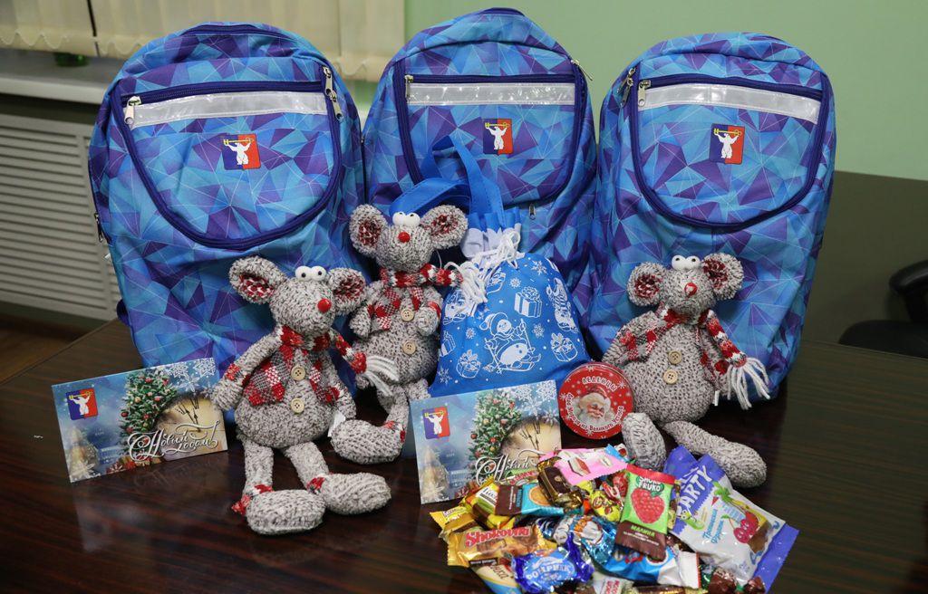 Мышка Букля, почти кило конфет, открытка-календарик и яркий рюкзак станут отличным новогодним подарком для норильской детворы.